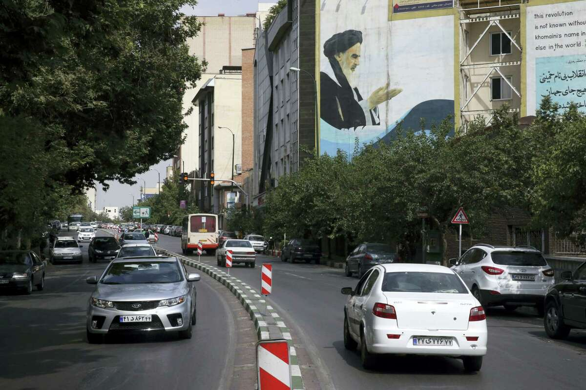 """Cars drive past a painting of late Iranian revolutionary founder Ayatollah Khomeini at Bahonar street in northern Tehran, Iran. Chevrolet, the U.S. car brand once advertised as the """"Heartbeat of America,"""" won't be rolling new models through the streets of Iran anytime soon despite the recent lifting of sanctions under a nuclear deal with world powers."""