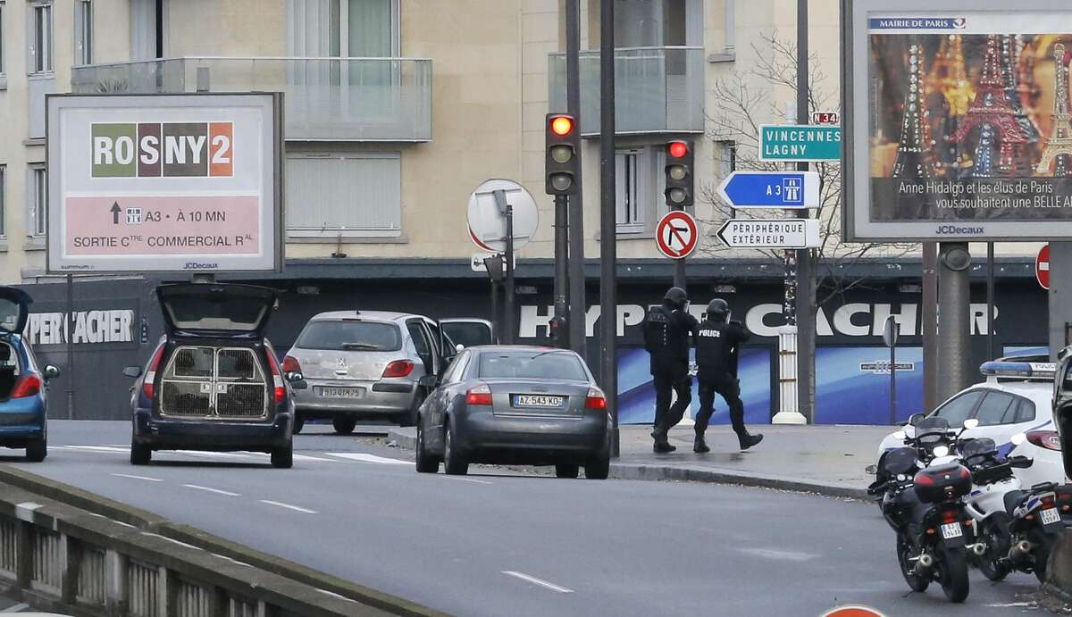 Police officers walk in front of an hostage-taking situation at a kosher market, seen in blue in background, in Paris, Friday Jan. 9, 2015. A police official says the man who has taken at least five people hostage in a kosher market in Paris appears to be linked to the newsroom massacre earlier this week that left 12 people dead. (AP Photo/Francois Mori)