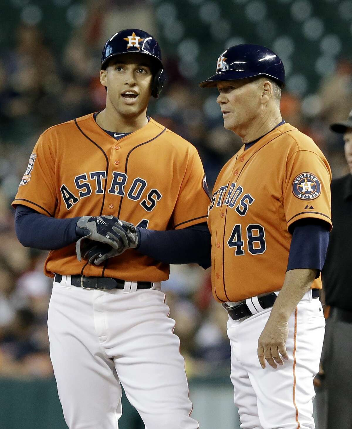 The Astros' George Springer, left, talks with first base coach Rich Dauer after getting a single against the Minnesota Twins in the his first at-bat off the DL on Friday in Houston.