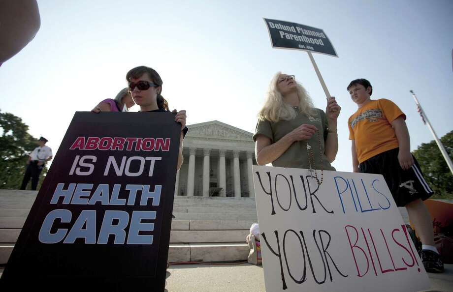 AP Photo/Evan Vucci, File In this June 28, 2012 photo, demonstrators pray outside the Supreme Court in Washington before a landmark decision on health care. Photo: AP / AP