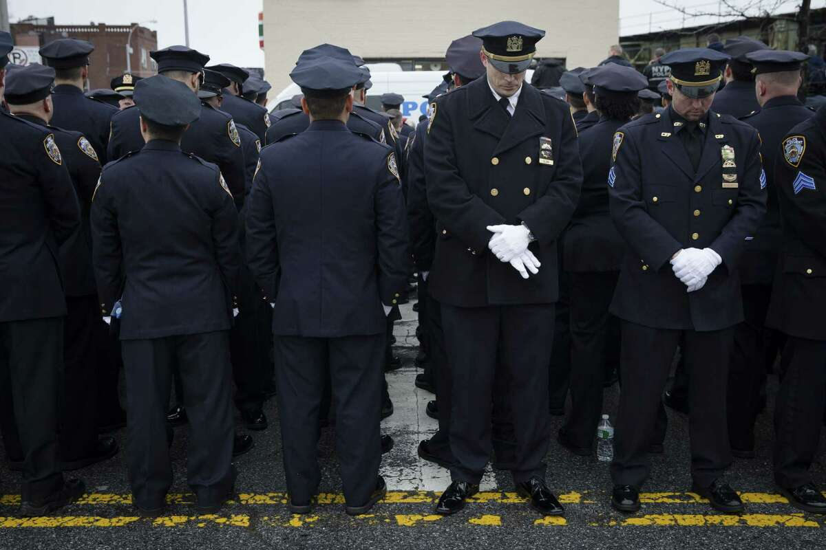 Some police officers turn their backs in sign of disrespect as Mayor Bill de Blasio speaks during the funeral of New York Police Department Officer Wenjian Liu at Aievoli Funeral Home on Sunday in the Brooklyn borough of New York.