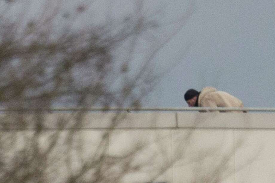 A man crawls on the roof of a building in Dammartin-en-Goele, northeast of Paris, where the two brothers suspected in a deadly terror attack were cornered, Friday, Jan. 9, 2015. Explosions and gunshots rang out and smoke rose outside a building where two brothers suspected in a newspaper massacre are holed up with a hostage. Photo: (Peter Dejong — The Associated Press) / AP 2015