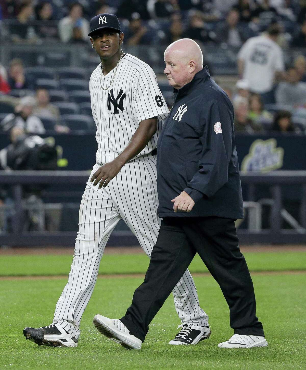 Yankees pitcher Luis Severino, left, walks off the field with head trainer Steve Donohue after giving up a two-run home run against the White Sox on Friday.