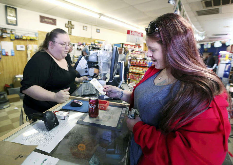 Lauren Fletcher, right, looks at the Powerball lottery ticket she purchased at the Country Store Friday, Jan. 8, 2016, in Odessa, Texas, as the multi-state jackpot reaches $800 million. With ticket sales doubling previous records, the odds are growing that someone will win Saturday's record jackpot, but if no one wins the top prize, next week's drawing is expected to soar past $1 billion. Photo: Edyta Blaszczyk/Odessa American Via AP / Odessa American