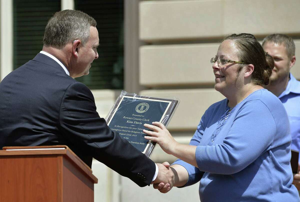 Pastor Jeffrey Fugate of the Clays Mill Road Baptist Church in Lexington, Ky., left, gives an award to Rowan County Clerk Kim Davis during a Religious Freedoms Rally at the Kentucky State Capitol in Frankfort Ky., Saturday, Aug. 22, 2015. Davis has been sued by The American Civil Liberties Union for denying marriage licenses to same-sex couples. She says her Christian faith prohibits her from signing the licenses.