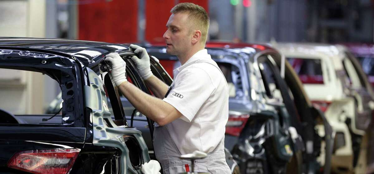 An employee of Audi works in the assembly line of the Audi production site in Ingolstadt, southern Germany, in 2013.