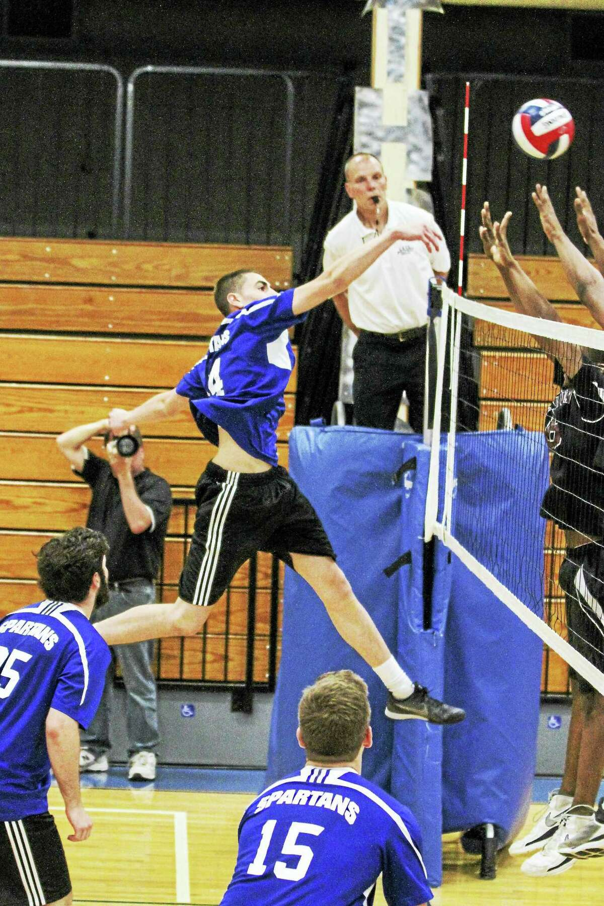 Lewis Mills' Anthony Licata sends a kill over Farmington's would-be blockers in a Spartan win at home Friday evening.