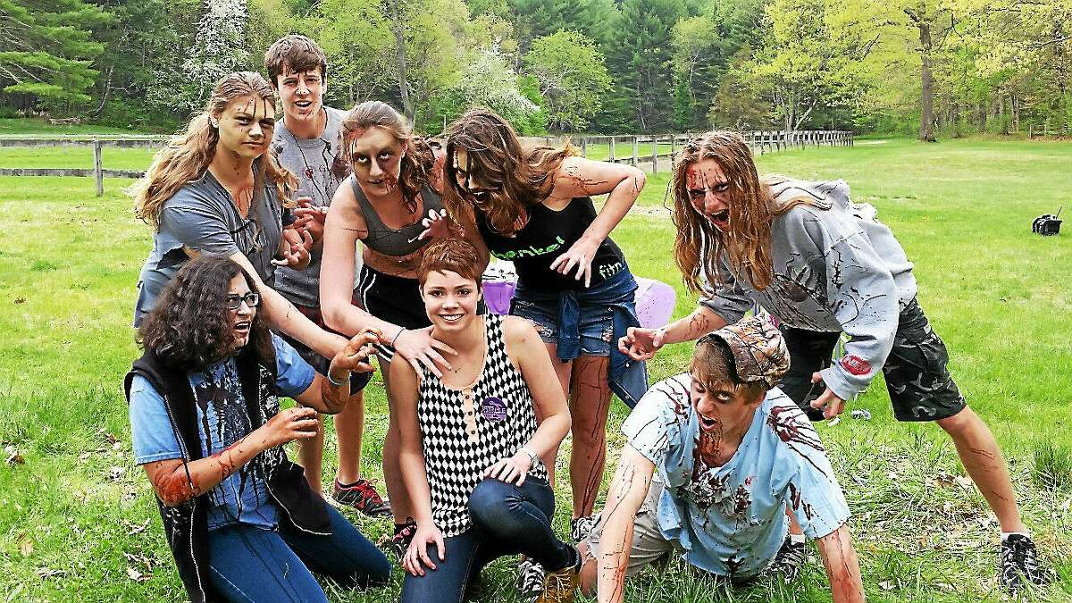 Shepaug Valley High School senior Krista Collins, 17, of Washington poses with volunteers wearing zombie costumes prior to the 5K Zombie Run Against Epilepsy on Saturday afternoon at Steep Rock Preservation at 2 Tunnel Road in Washington Depot.