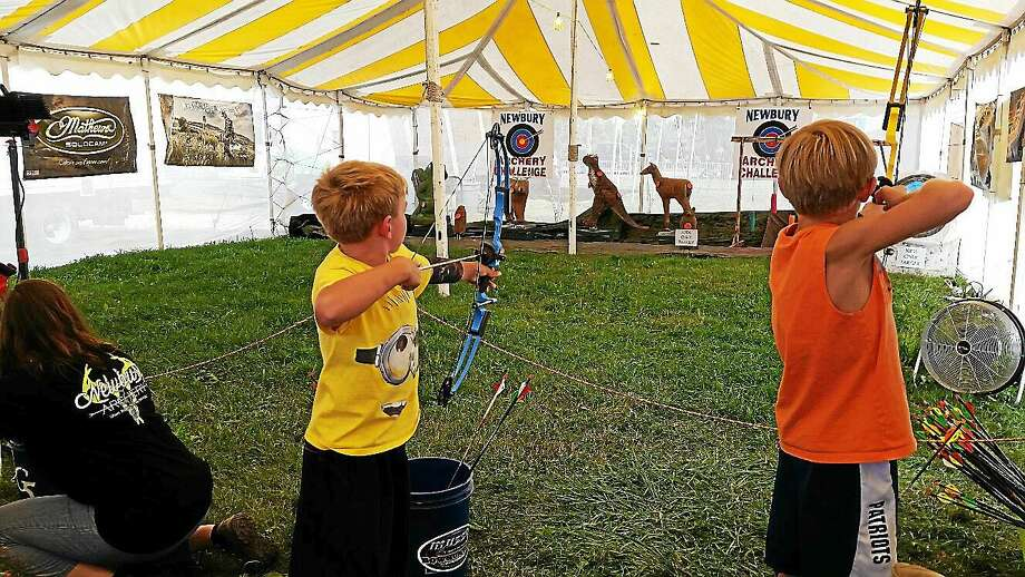 Gavin Welch, 8, and his brother Brayden, 10, both of Burlington, prepare to hit their target during an archery contest at the 103rd annual Goshen Fair at 116 Old Middle St. in Goshen on Saturday afternoon. Photo: Noel Ambery — Register Citizen