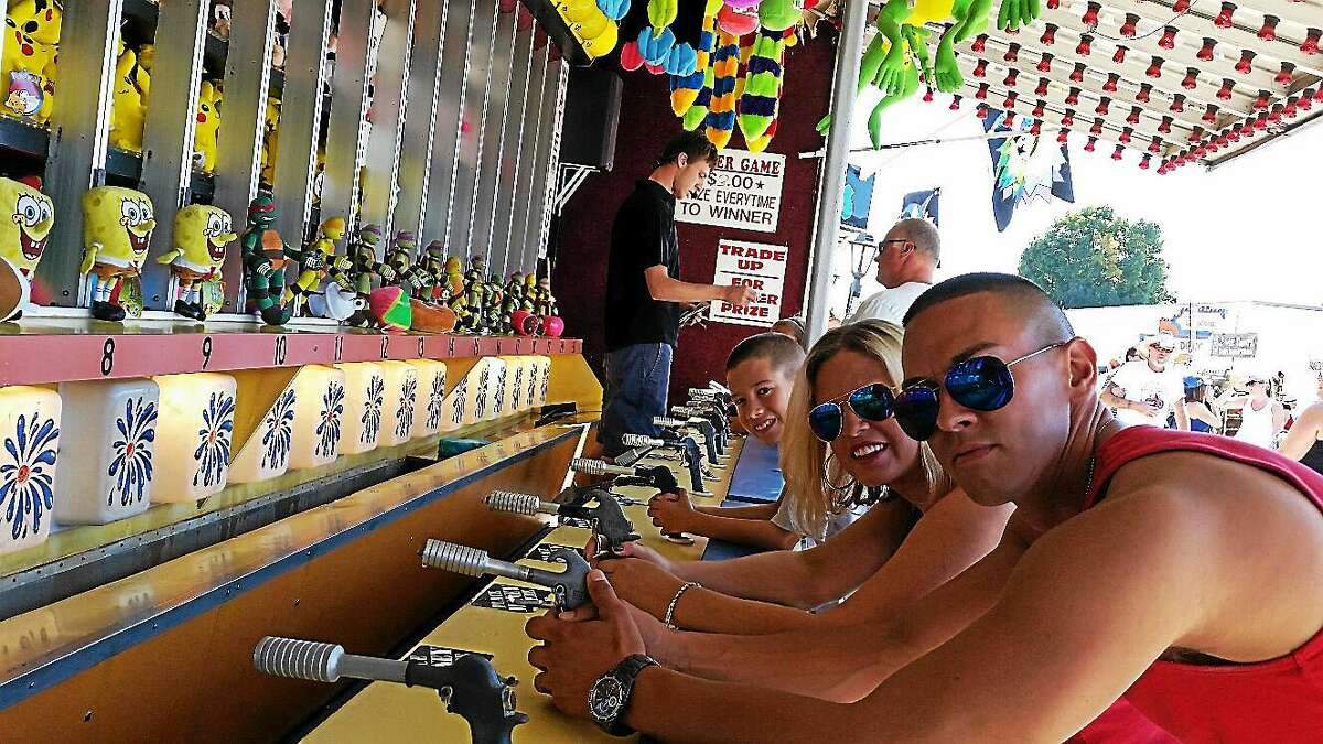 Jake Medeiros, 8, his mother, Kate; and Tony Rios, all of Bethel, try their hand at carnival shooting at the 103rd annual Goshen Fair at 116 Old Middle St. in Goshen on Saturday afternoon.