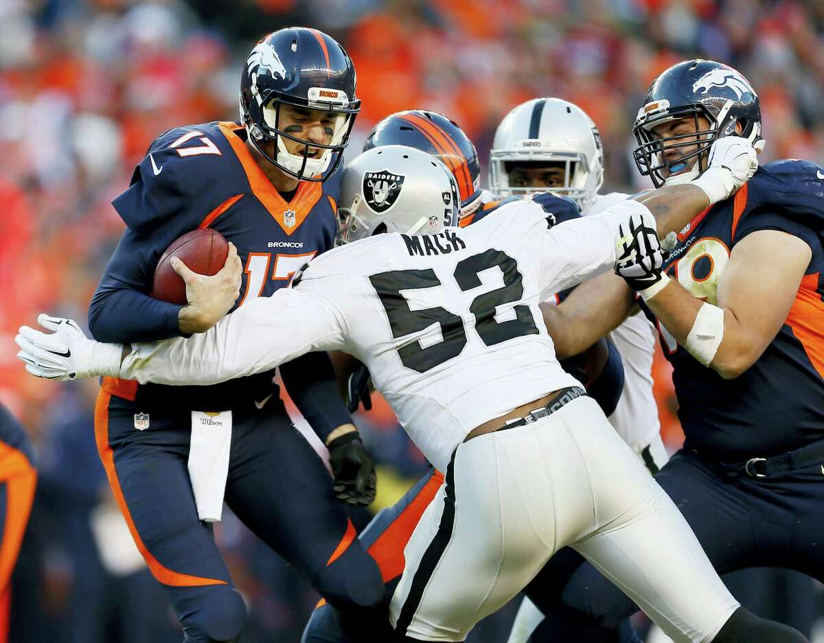 FILE - In this Dec. 13, 2015, file photo, Denver Broncos quarterback Brock Osweiler (17) is sacked by Oakland Raiders defensive end Khalil Mack (52) during the second half of an NFL football game, in Denver. Khalil Mack has become the first selection at two positions in the same year, while Adrian Peterson and J.J. Watt are unanimous choices for the 2015 Associated Press NFL All-Pro Team. (AP Photo/Joe Mahoney, File)