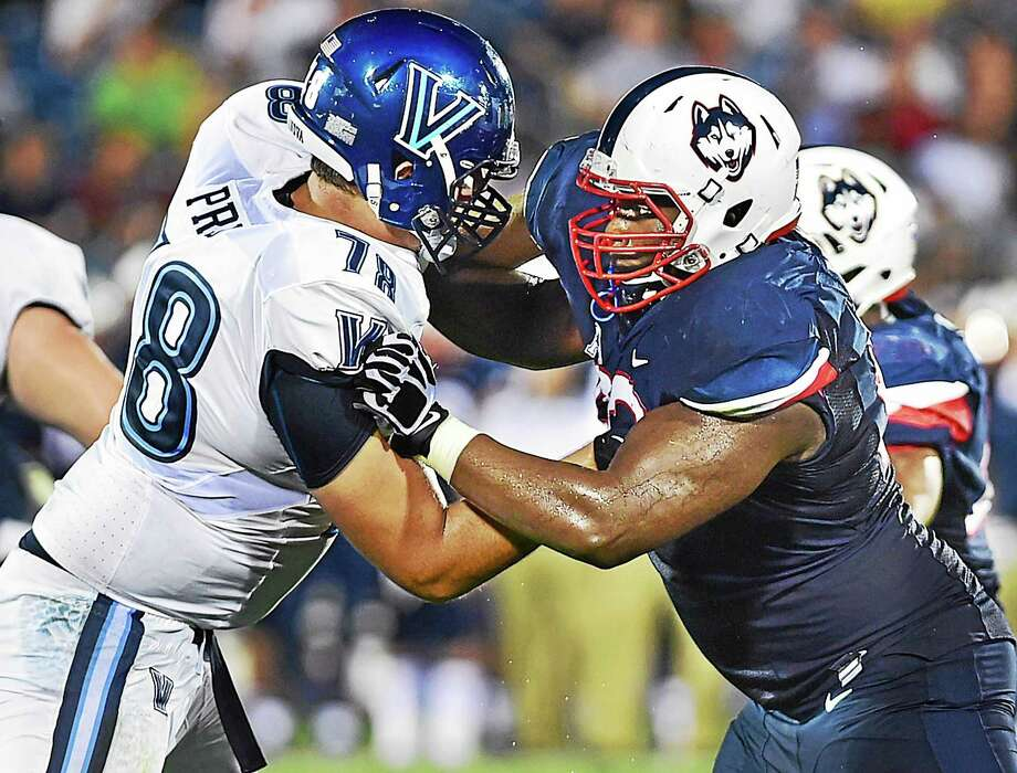 UConn defensive lineman Folorunso Fatukasi battles Villanova's Jake Prus during the Huskies' 20-15 win Thursday night. Fatukasi is suspended for the first half of UConn's next game with Army after getting ejected late in the fourth quarter. Photo: Catherine Avalone — Register  / Catherine Avalone/New Haven Register