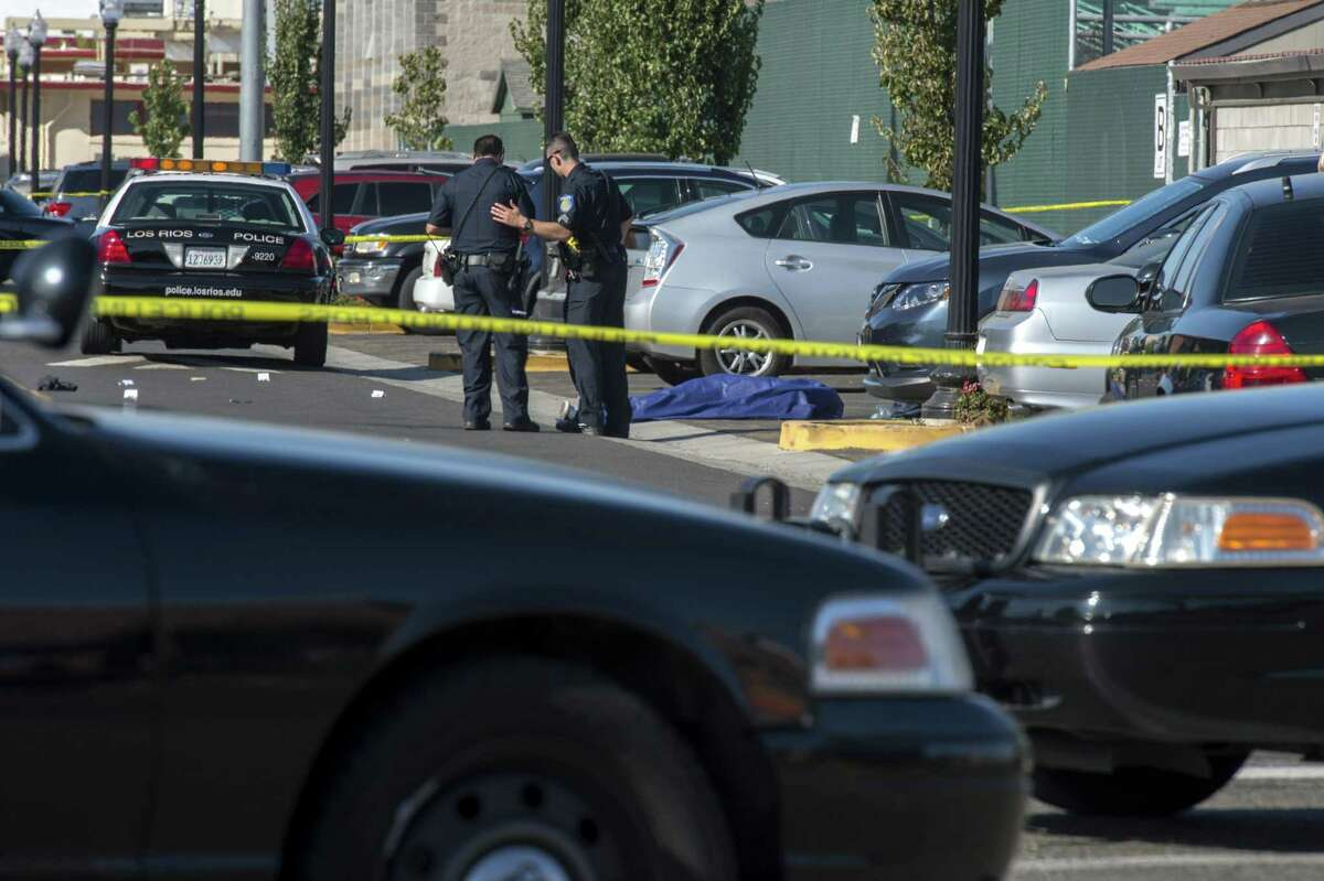 Police officers stand near the body of a victim killed in a shooting at Sacramento City College, Thursday, Sept. 3, 2015, in Sacramento, Calif. The shooting occurred in a parking lot near the baseball field on the college campus.