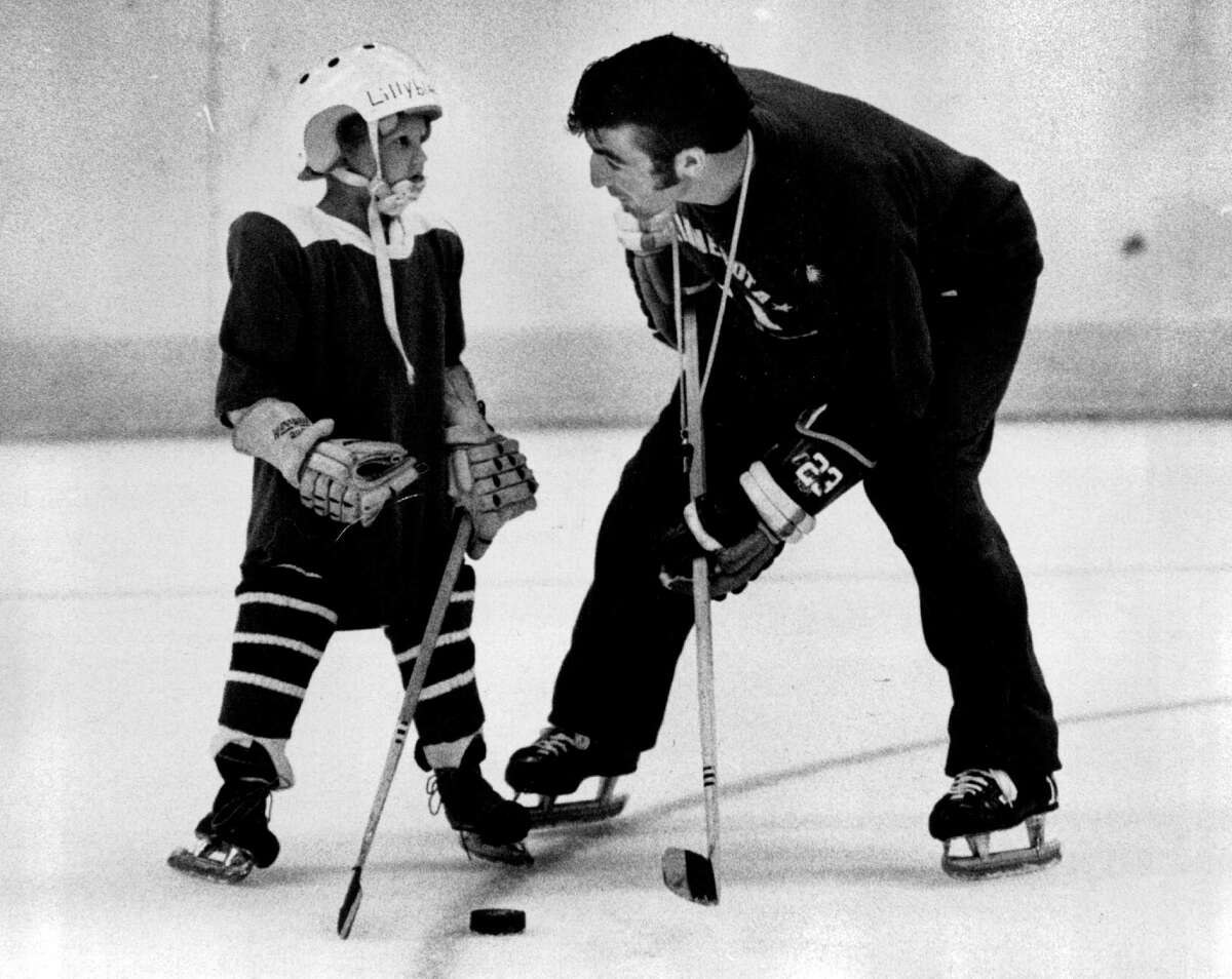 In this June 24, 1971 photo, J.P. Parise gives advise to 5-year-old Mike Lillyblad at the Minnesota North Stars hockey clinic in Bloomington, Minn. Parise died from lung cancer on Wednesday night at the age of 73.