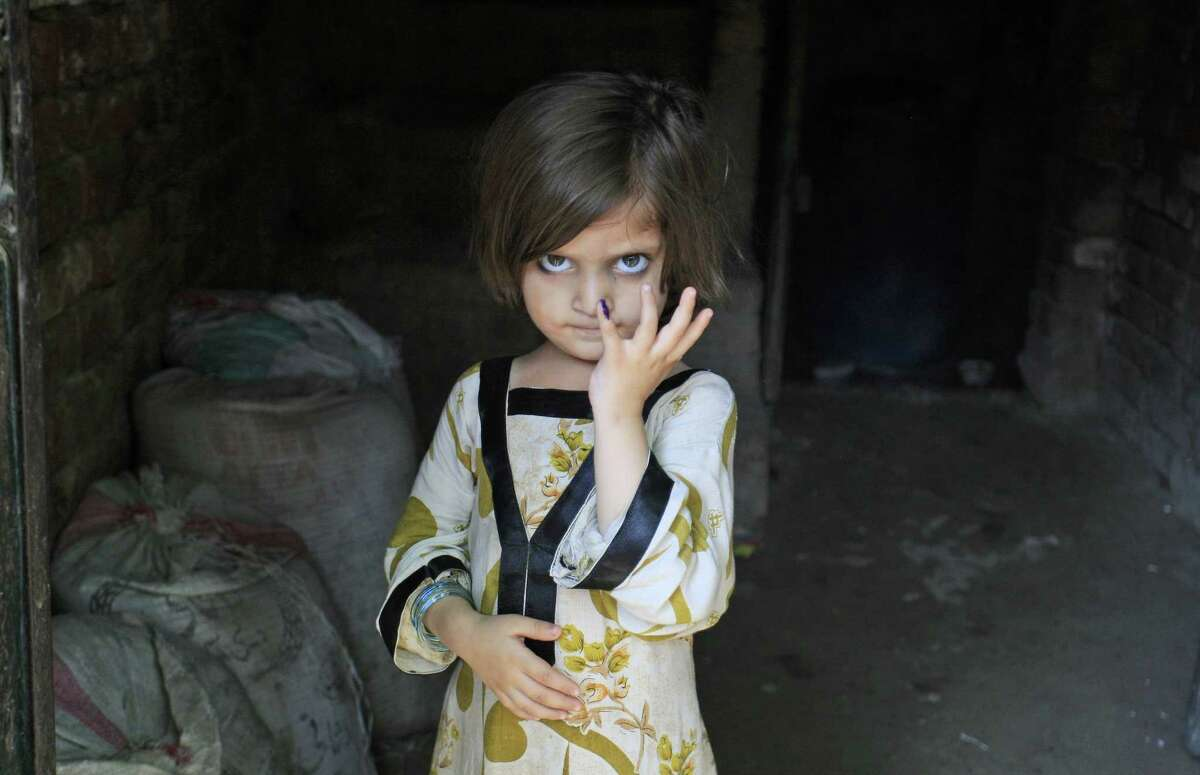 A Pakistani girl shows her finger marked with ink after receiving a polio vaccine from a health worker in Lahore, Pakistan, in this 2012 photo.