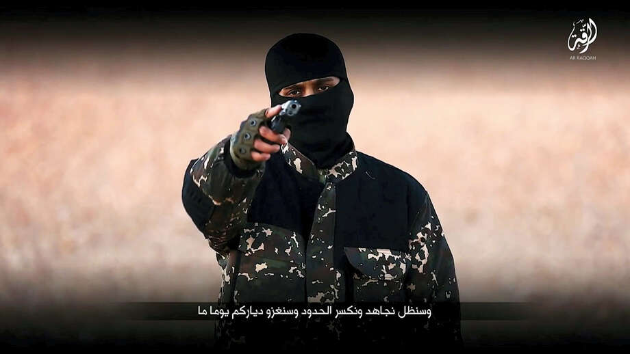 This undated image taken from video and posted online by Communications Arm of Islamic State, circulating online Sunday Jan. 3, 2016, purports to show a member of the Islamic State group brandishing a gun and talking to the camera, before Islamic State group members seem to execute five men they accuse of spying for Britain in Syria. The video could not be independently verified, but bears the markings of IS media wing. A Syrian human rights group says another IS member publicly executed his own mother in front of hundreds of people. Photo: Militant Video Via AP   / Communications Arm of Islamic State group
