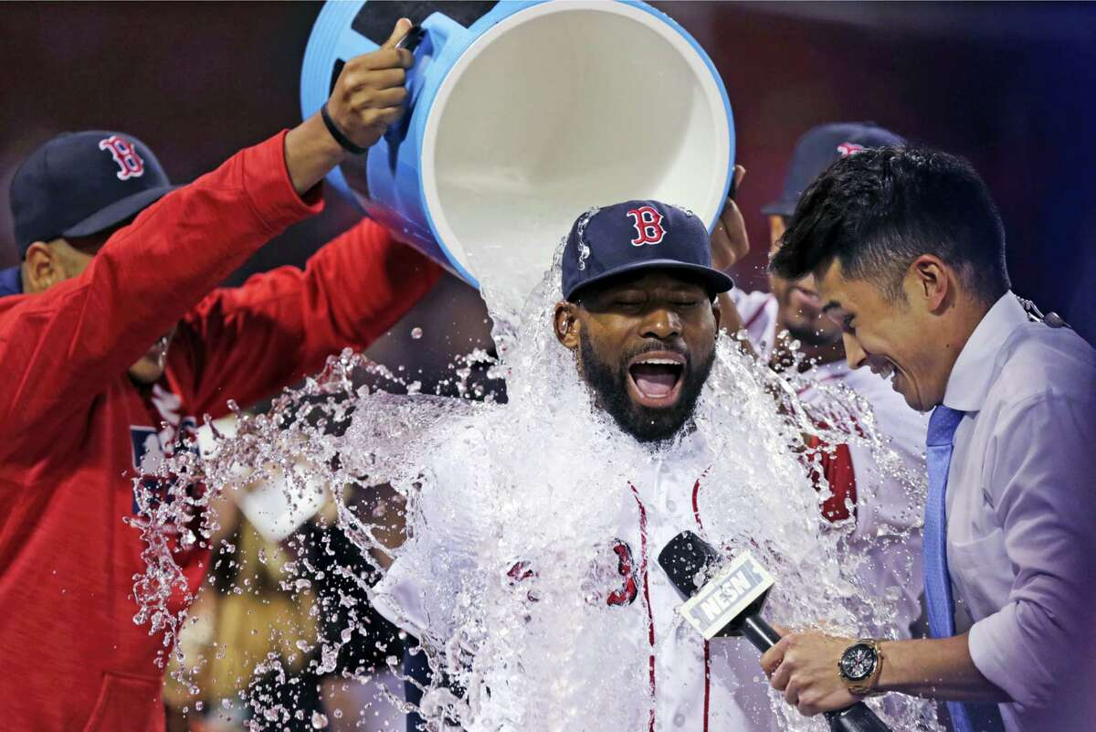 Boston Red Sox's Jackie Bradley Jr. is doused with a bucket of ice water by teammates after a 13-3 win against the Oakland Athletics at Fenway Park in Boston, Wednesday, May 11, 2016. Bradley had two home runs and six RBI's in the game. At right is baseball sideline reporter Gary Striewski. (AP Photo/Charles Krupa)