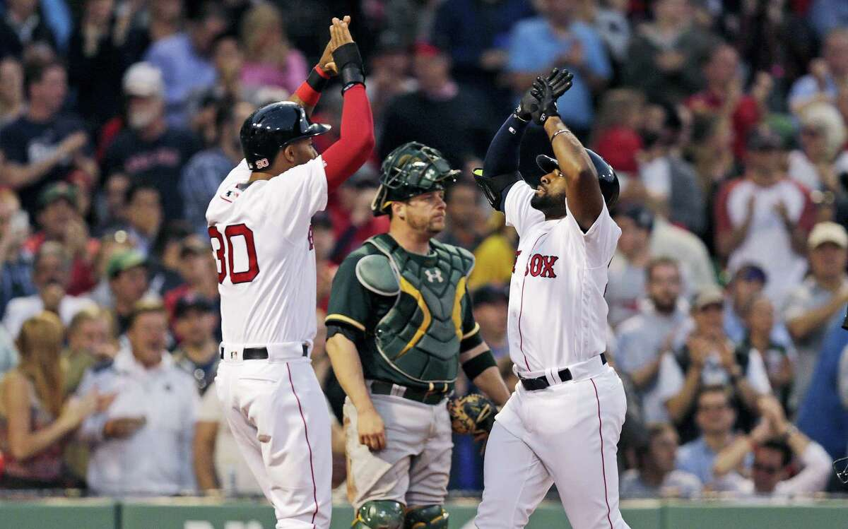 Boston Red Sox's Jackie Bradley Jr., right, is congratulated by Chris Young after his three-run home run during the second inning of a baseball game at Fenway Park in Boston, Wednesday, May 11, 2016. At center is Oakland Athletics catcher Stephen Vogt. (AP Photo/Charles Krupa)