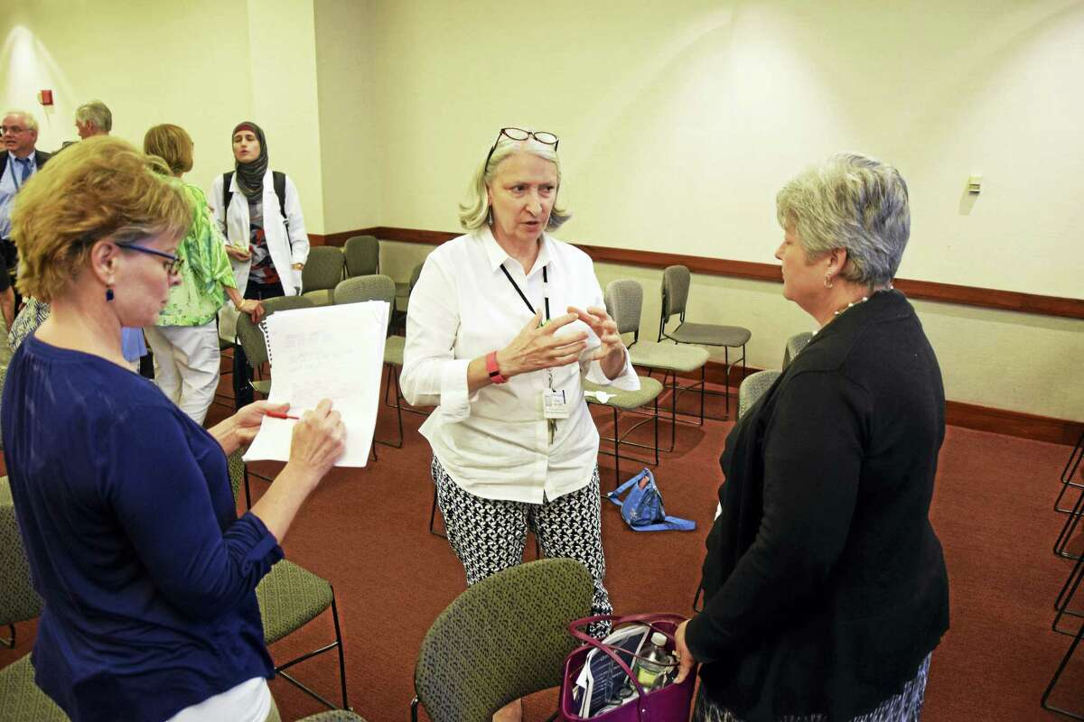 Daun Barrett, center, director of Community Outreach and Parish Nursing at Griffin Hospital in Derby, gathers contact information from nurses concerned about asthma after a community meeting at the hospital Aug. 9.