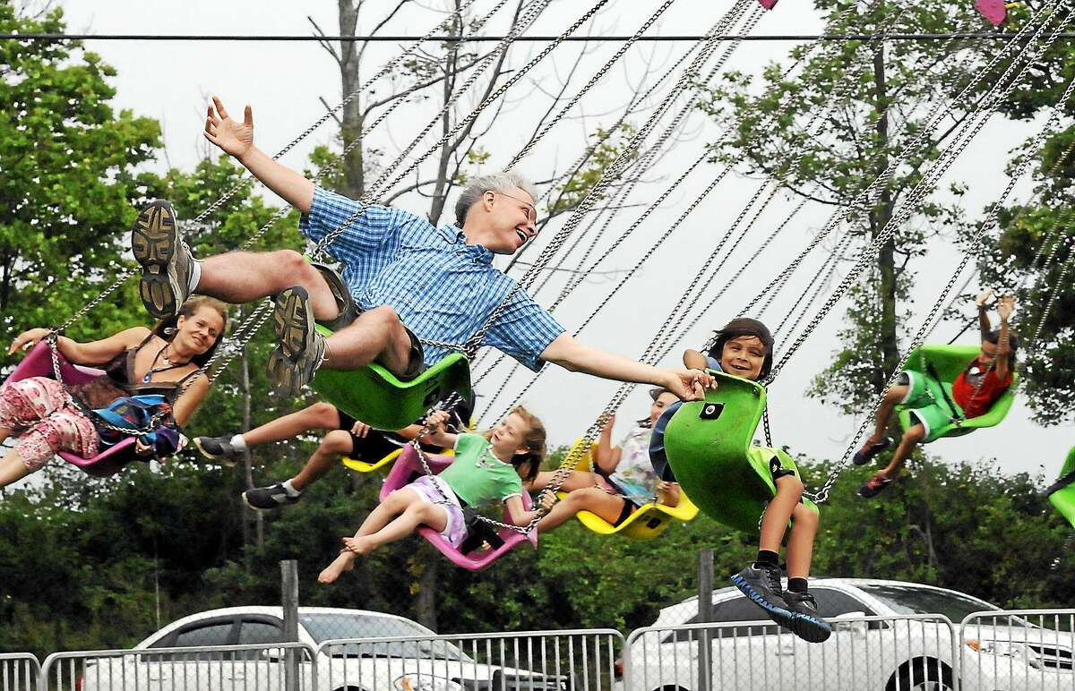 John Wardzala holds hands with his son while on the swings at the Goshen Fair.