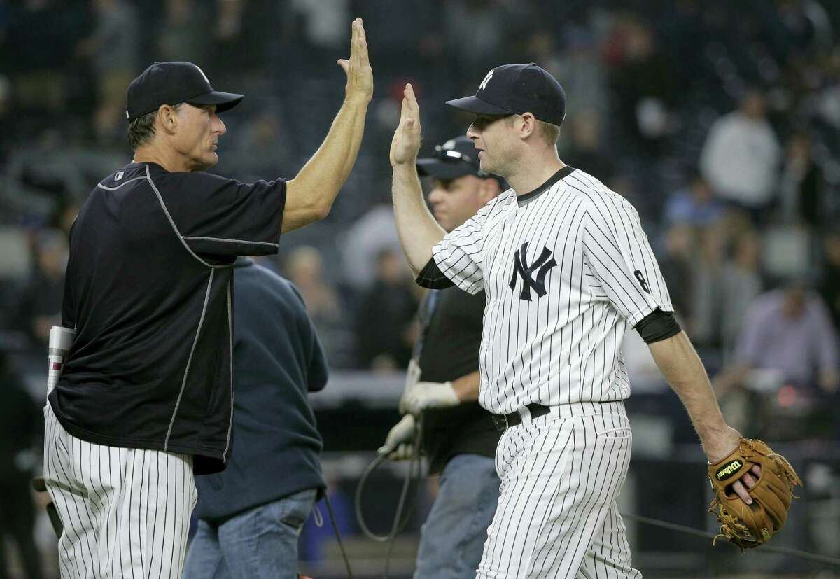 New York Yankees third baseman Chase Headley, right, high-fives hitting coach Alan Cockrell after the Yankees defeated the Kansas City Royals 7-3 Thursday in New York.