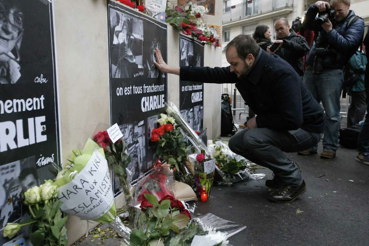 """A man reacts as he squats down near flowers laying outside the Charlie Hebdo newspaper in Paris, Thursday, Jan.8, 2015, a day after masked gunmen stormed the offices of a satirical newspaper and killed 12 people. Protesters in some U.S. cities ó repeating the viral online slogan """"Je Suis Charlie"""" or """"I Am Charlie""""ó demonstrated against the deadly terror attack on a Paris newspaper office, joining thousands around the world who took to the streets to rally against the killings. Poster reads: We really are all Charlie. (AP Photo/Francois Mori)"""