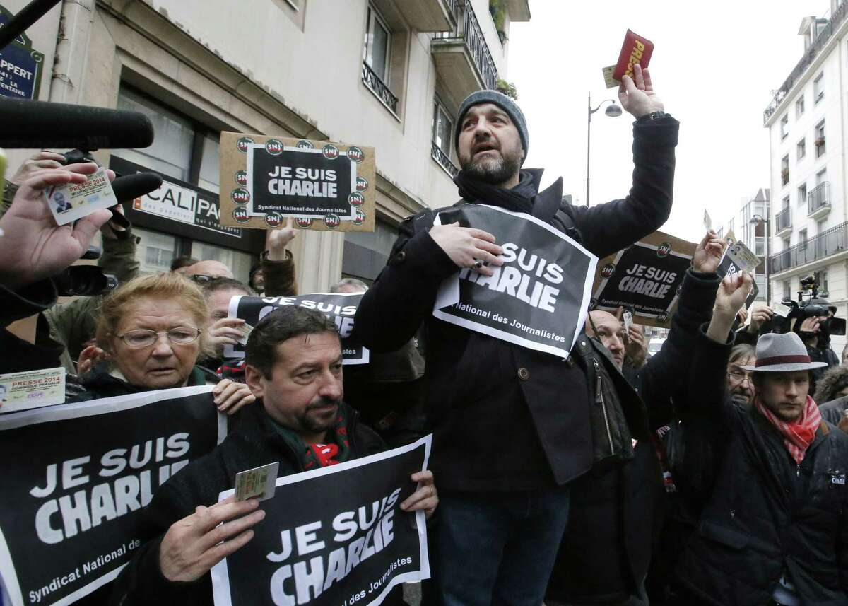"""Journalist show their press cards during a minute of silence outside the Charlie Hebdo newspaper in Paris, Thursday, Jan.8, 2015, a day after masked gunmen stormed the offices of a satirical newspaper and killed 12 people. Protesters in some U.S. cities Û repeating the viral online slogan """"Je Suis Charlie"""" or """"I Am Charlie""""Û demonstrated against the deadly terror attack on a Paris newspaper office, joining thousands around the world who took to the streets to rally against the killings. (AP Photo/Francois Mori)"""
