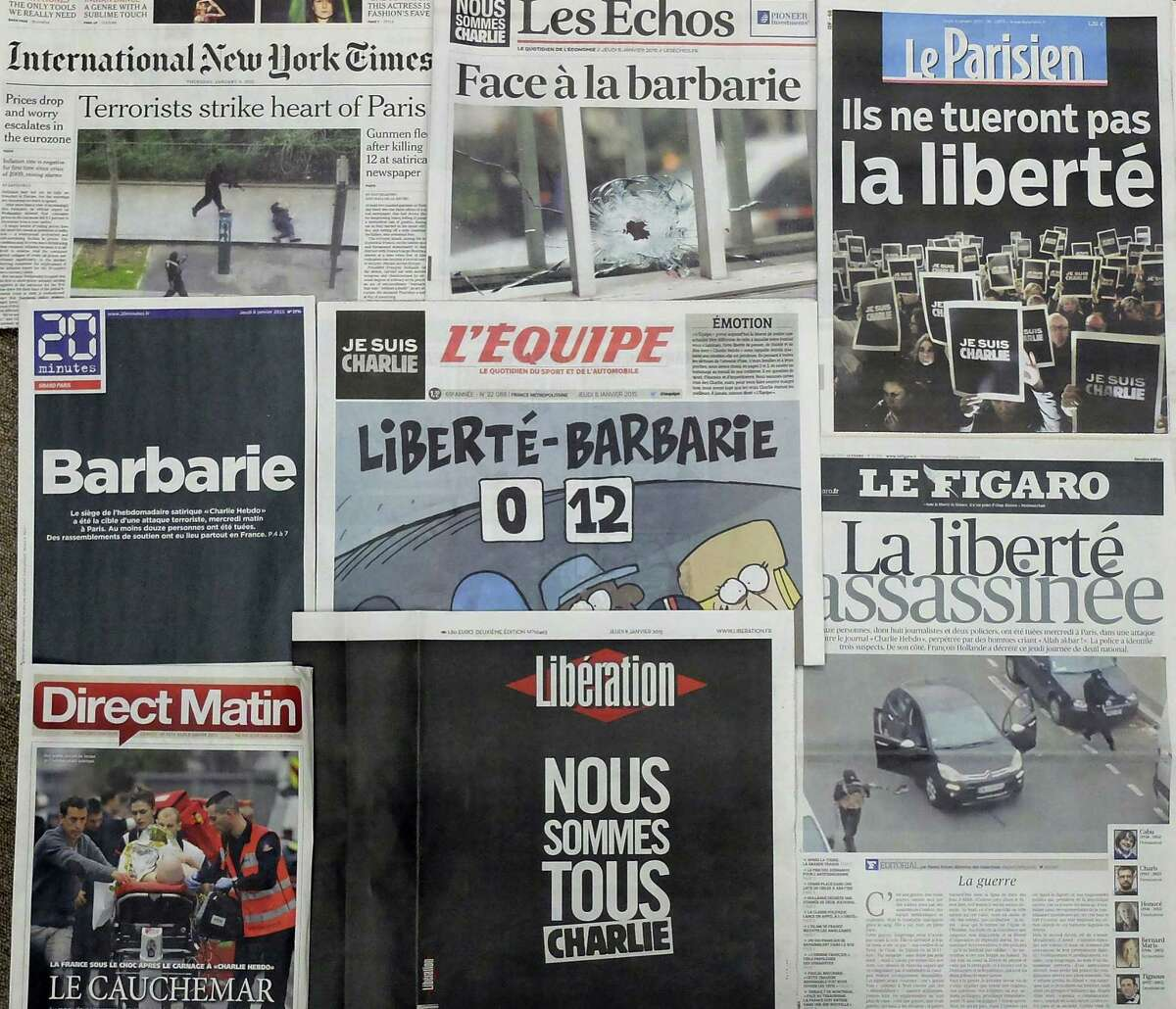 """Frontpages of French newspapers reporting about Wednesday's attack on a satirical newspaper in Paris are displayed in Paris Thursday, Jan. 8, 2015. Police hunted Thursday for two heavily armed men, one with possible links to al-Qaida, in the methodical killing of 12 people at the Charlie Hebdo that caricatured the Prophet Muhammed. The prime minister said the possibility of a new attack """"is our main concern"""" and announced several overnight arrests. (AP Photo/Bertrand Combaldieu)"""