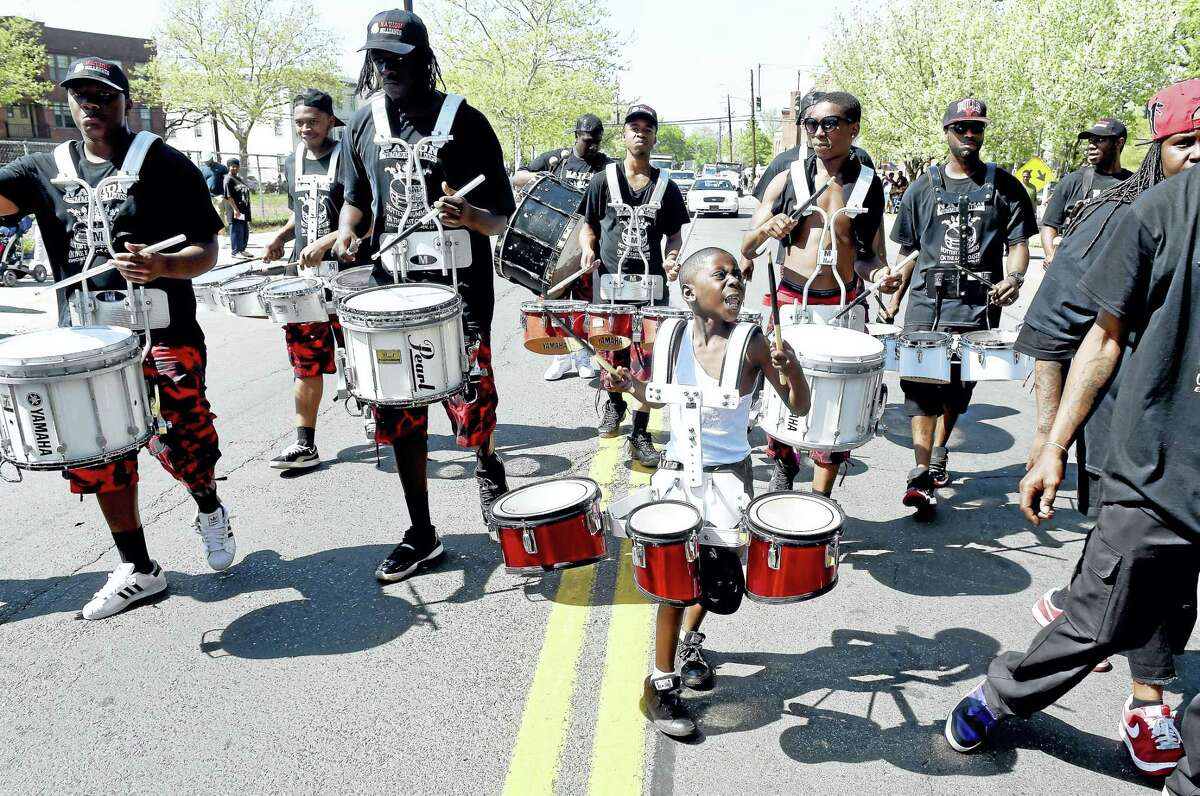 Young Julian Threadgill, center, drums with the New Haven-based Nation Drill Squad and Drum Corp during last year's parade.