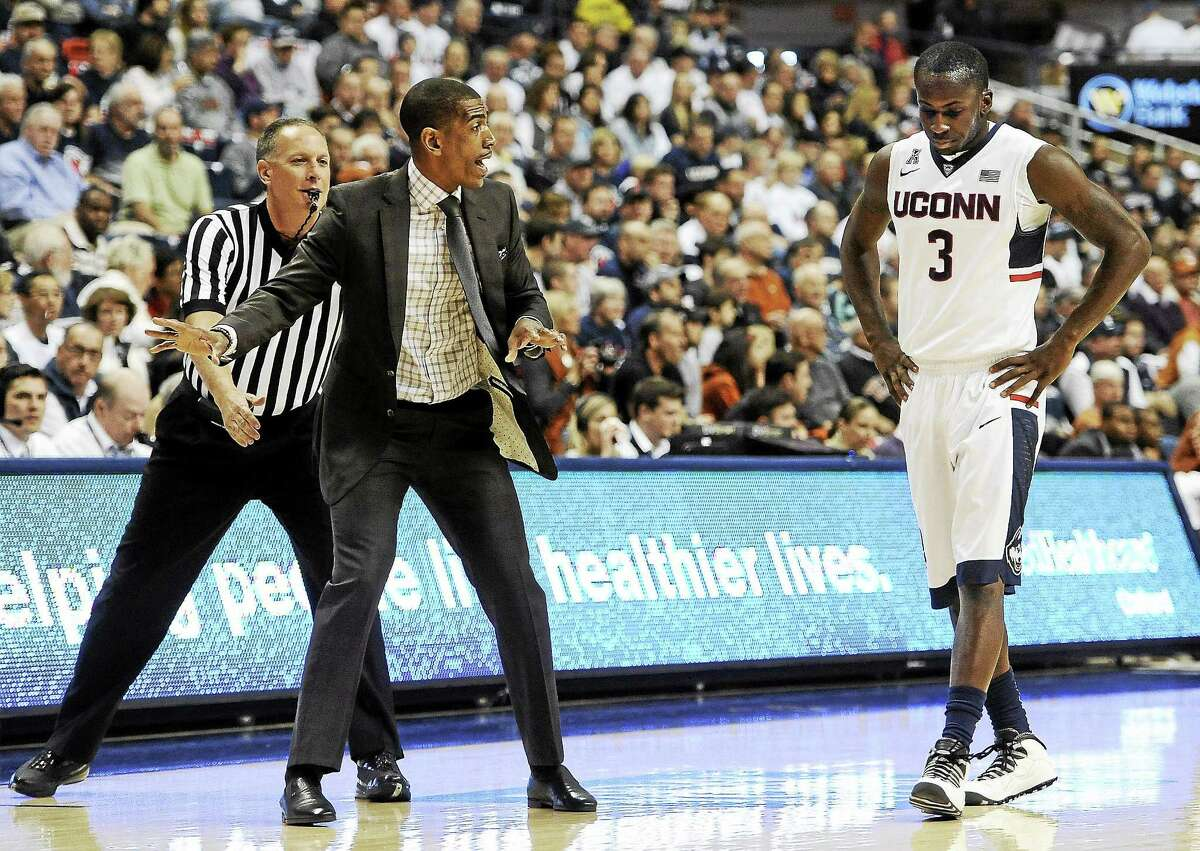 UConn coach Kevin Ollie, left, talks with Terrence Samuel during a game last season.