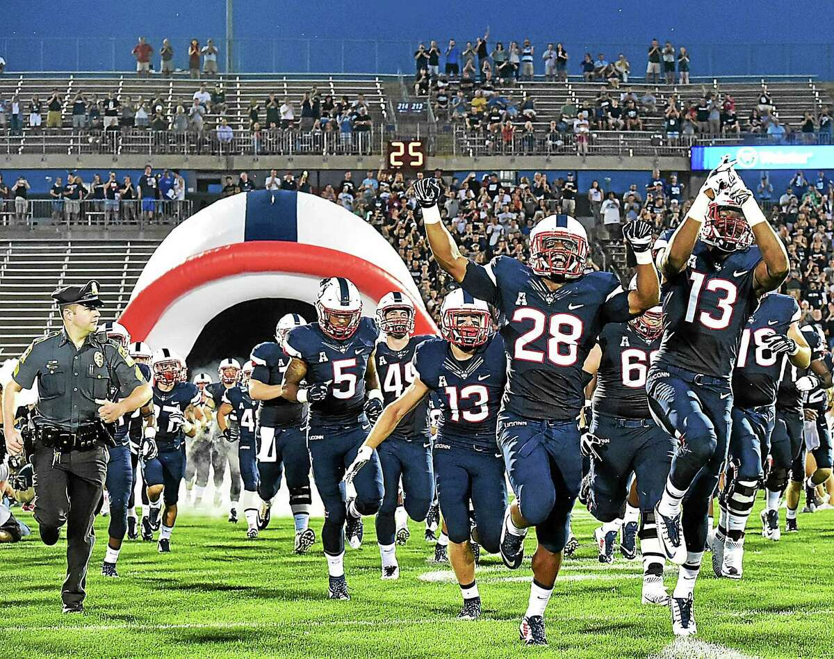 UConn players run onto the field for their season opener against Villanova.