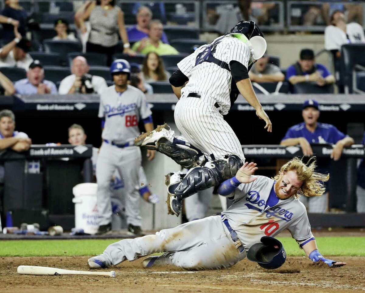 Los Angeles Dodgers' Justin Turner, right, slides past New York Yankees catcher Gary Sanchez to score during the ninth inning Wednesday in New York. The Dodgers won 2-0.