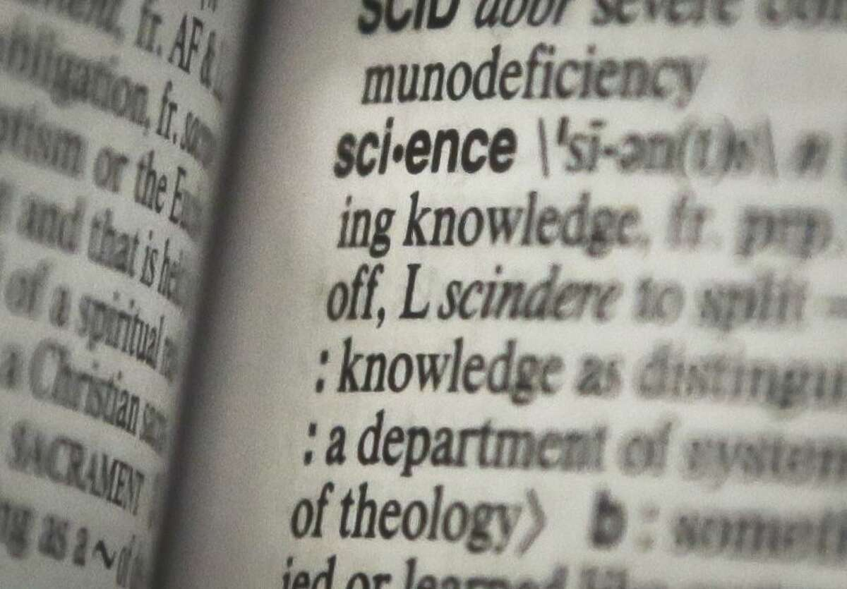 """The word """"science"""" is seen on a page of a Merriam-Webster dictionary."""