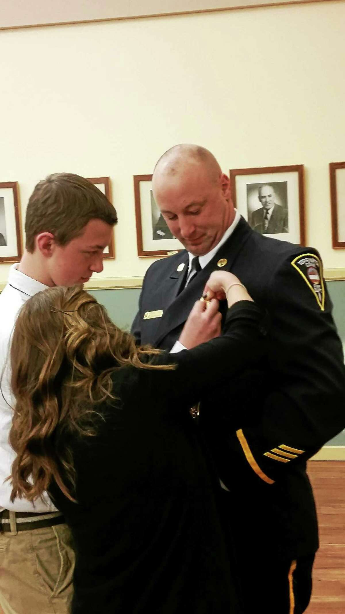 Fire Capt. David Casper receives his pin from members of his family Wednesday night at a Board of Public Safety meeting in Torrington.