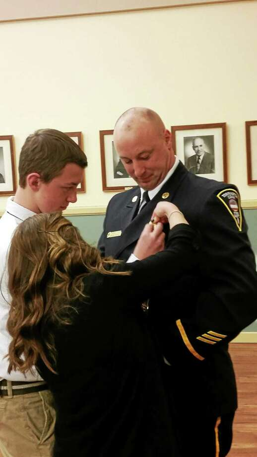 Fire Capt. David Casper receives his pin from members of his family Wednesday night at a Board of Public Safety meeting in Torrington. Photo: Amanda Webster — The Register Citizen