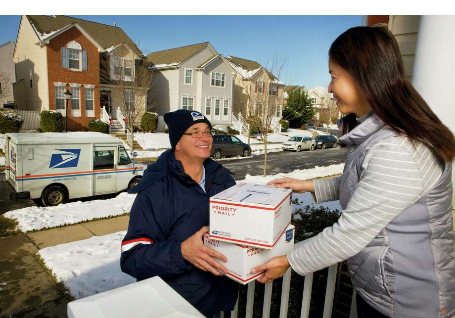 U.S. Postal Service letter carrier delivering packages during the holidays. Photo: PRNewsFoto/U.S. Postal Service  / U.S. Postal Service