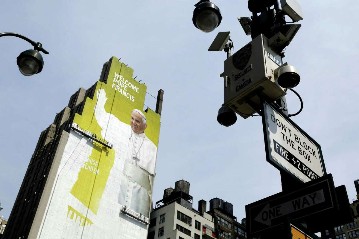 In this Aug. 30, 2015 file photo, sign painters work on a portrait of Pope Francis on the side of a New York City office building as some surveillance cameras operated by the New York City Police Department can be seen on lamp posts at either side. New York Police Commissioner William Bratton says local, state and federal law enforcement face an ìunprecedented challenge,î ensuring the pontiffís safety as he address over 160 heads of state at the United Nations, presides over a 9/11 memorial service, rides through Central Park and celebrates Mass at Madison Square Garden.