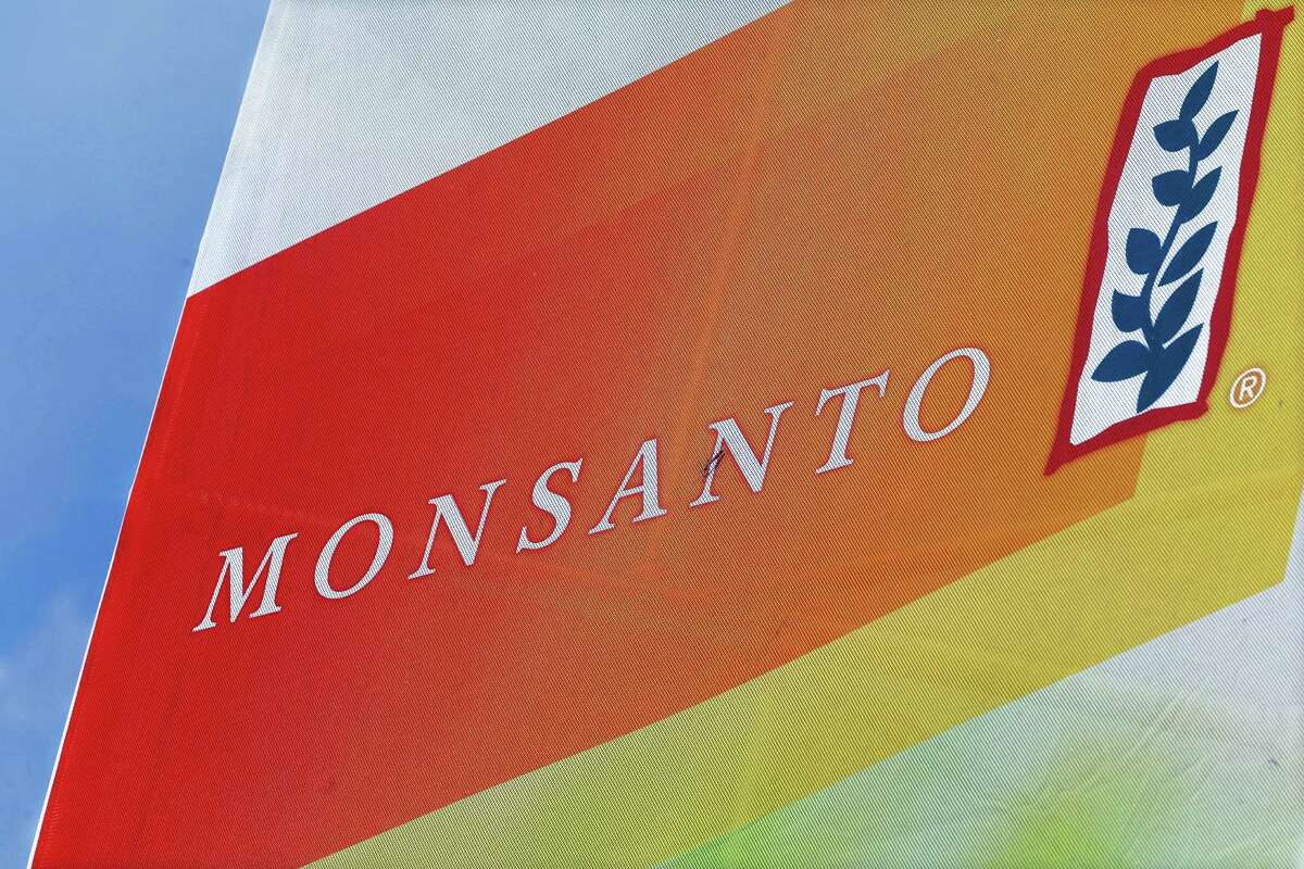 This Aug. 31, 2015 photo, shows the Monsanto logo on display at the Farm Progress Show in Decatur, Ill. German drug and farm chemical company Bayer AG said it signed a deal Wednesday, Sept. 14, 2016 to acquire seed and weed-killer company Monsanto for about $66 billion in cash.