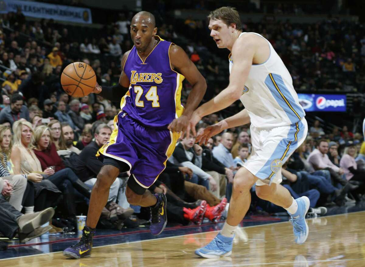 Los Angeles Lakers guard Kobe Bryant rushes past Nuggets center Timofey Mozgov during a Dec. 30 game in Denver.