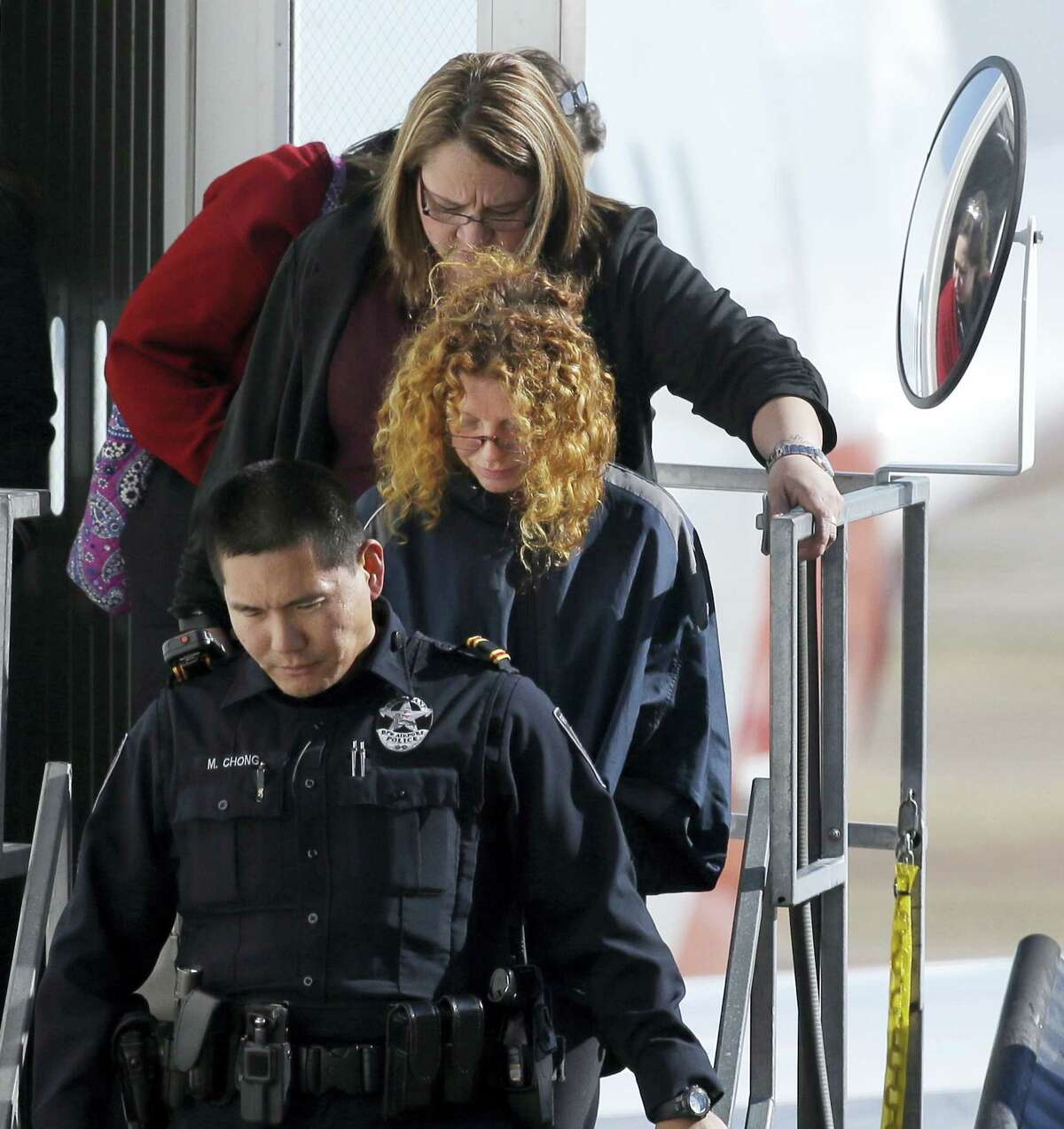 """Tonya Couch is escorted off a flight after her arrival to the Dallas/Fort Worth International Airport in Grapevine, Texas, Thursday, Jan. 7, 2016. Couch, mother of a fugitive teenager known for using an """"affluenza"""" defense in a deadly drunken-driving case, waived extradition and was sent to Texas from California to face a charge of hindering the apprehension of a felon."""
