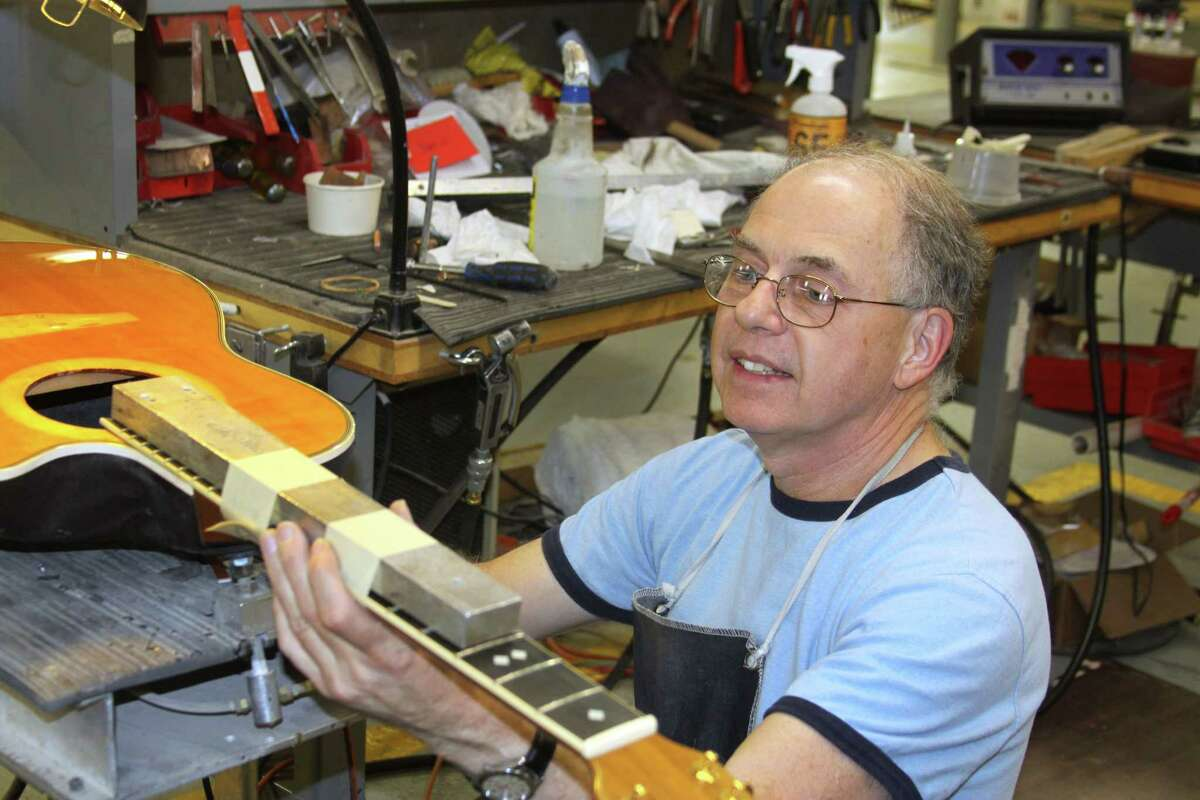 Ovation Guitars employee Mike DeNoi reattaches the neck of a customer's guitar at the factory in New Hartford. The factory that produced Ovation guitars for nearly a half century before closing last year will be making the renown instruments once again, thanks to the efforts of a factory employee who maintained the factory on his own in hopes a new buyer would revive it.