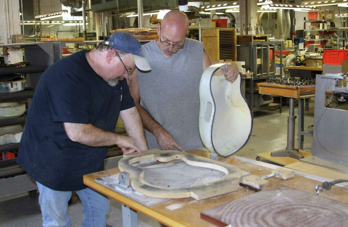 Ovation Guitars plant manager Darren Wallace, left, and Joe Martocchio discuss the manufacture of a guitar at the reopened factory in New Hartford.