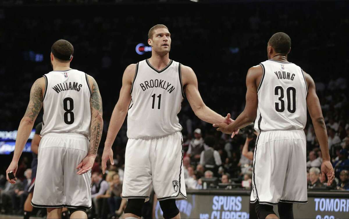 Brooklyn Nets center Brook Lopez reacts with teammates Thaddeus Young and Deron Williams during the second half of Game 6 against the Atlanta Hawks on Friday in New York.