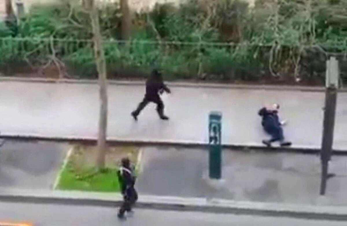 Masked gunman run towards a victim of their gun fire outside the French satirical newspaper Charlie Hebdo's office, in Paris, Wednesday, Jan. 7, 2015. Paris residents captured chilling video images of two masked gunmen shooting a police officer after an attack at a French satirical newspaper. In the video, the gunmen armed with assault rifles are seen running up to an injured police officer, who lies squirming on the ground. The police officer raises his hands up before one of the assailants shoots him in the head at a close range.