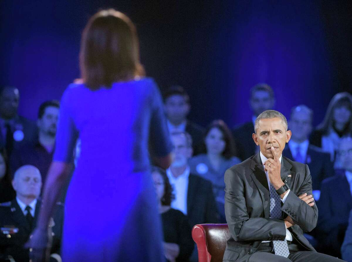 President Barack Obama, right, listens to a question from Taya Kyle, left, widow of U.S. Navy SEAL Chris Kyle, during a CNN televised town hall meeting hosted by Anderson Cooper at George Mason University in Fairfax, Va., Thursday, Jan. 7, 2016. Obama's proposals to tighten gun controls rules may not accomplish his goal of keeping guns out of the hands of would-be criminals and those who aren't legally allowed to buy a weapon. In short, that's because the conditions he is changing by executive action are murkier than he made them out to be.