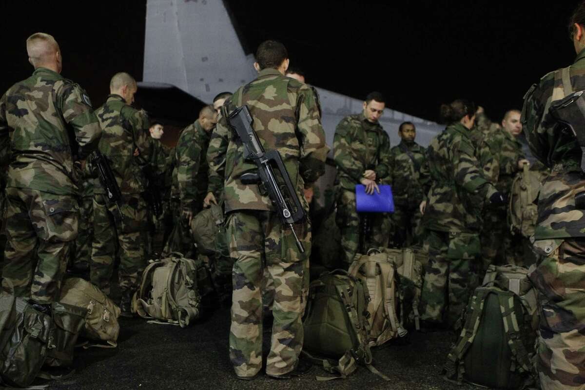"""French soldiers disembark at Le Bourget airport, north of Paris, as part of deployment of soldiers to enhance security in Paris, Wednesday, Jan. 7, 2015. Three masked gunmen shouting """"Allahu akbar!"""" stormed the Paris offices of a satirical newspaper, Charlie Hebdo, Wednesday, killing at least 12 people, including its editor, before escaping in a car. It was France's deadliest postwar terrorist attack."""