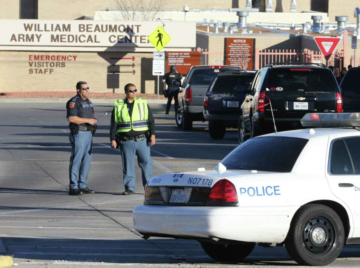 Police officers guard an entrance to the Beaumont Army Medical Center/El Paso VA campus during the search for a gunman Tuesday, Jan. 6, 2014. (AP Photo/The El Paso Times, Victor Calzada)