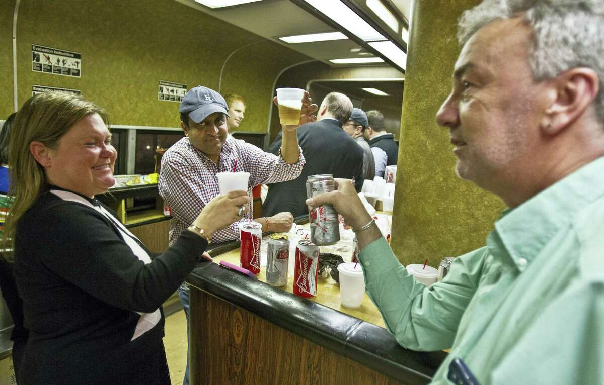 In this May 8, 2014, photo, Nan Buziak Lexow, left, Srikanth Reddy, center, and Mark DeMonte, right, raise a toast while riding the bar car on the 7:07 p.m. train from Grand Central Terminal in New York to New Haven, Conn. The bar cars were retired from Metro-North's New Haven Line after the afternoon rush hour.