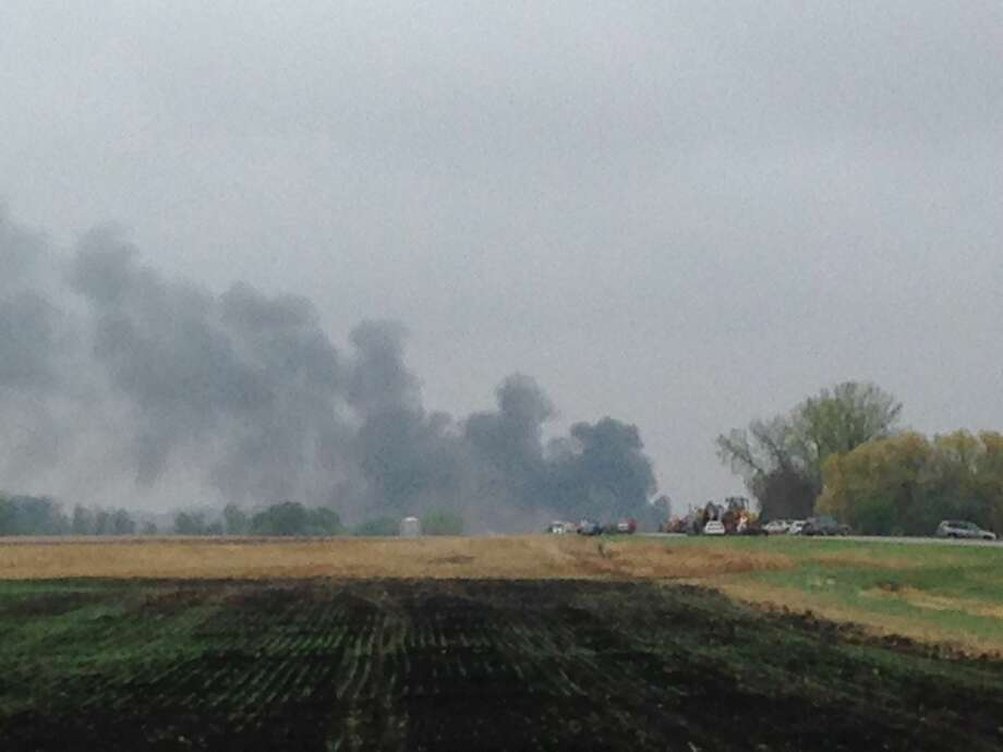 Smoke rises in the background past a field after BNSF Railway oil train derailed and caught fire in rural area about two miles from Heimdal, N.D. The central North Dakota town had to been evacuated due to the derailment and fire. Photo: (Tom Stromme/The Bismarck Tribune Via AP) / The Bismarck Tribune