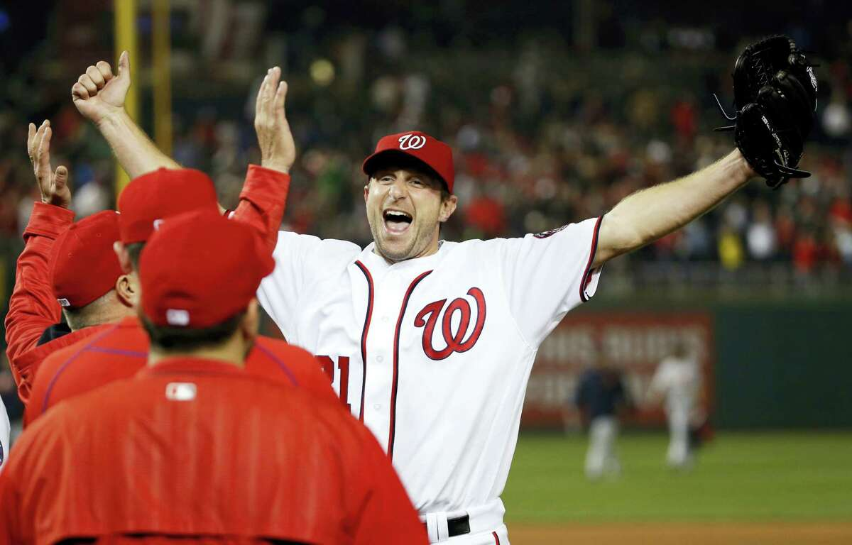 Washington Nationals starting pitcher Max Scherzer celebrates with his teammates after a baseball game against the Detroit Tigers at Nationals Park, Wednesday in Washington. Scherzer struck out 20 batters, tying the major league nine-inning record. The Nationals won 3-2.